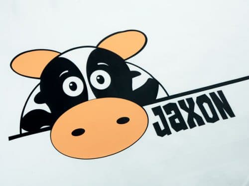 """A cute cow with the name """"Jaxon"""" on a pillowcase- the cow is made from ThermoFlex® Plus Matte in Black and Peach"""